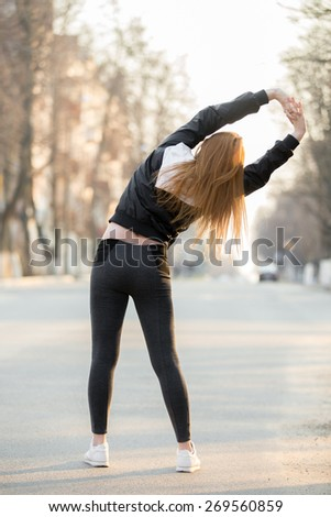 Runner girl doing warming up exercises for spine before morning jogging on the street, stretching, preparing for running, back view - stock photo