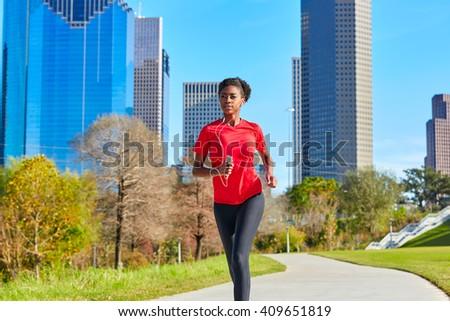 Runner girl running and listening music earphones in the city park - stock photo
