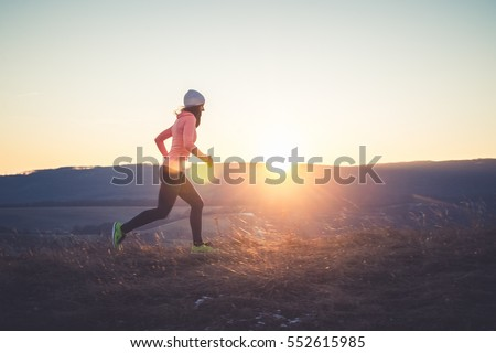 Runner girl running on top of the hill