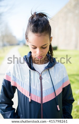 Runner hispanic woman portrait outdoors. She is looking down. - stock photo
