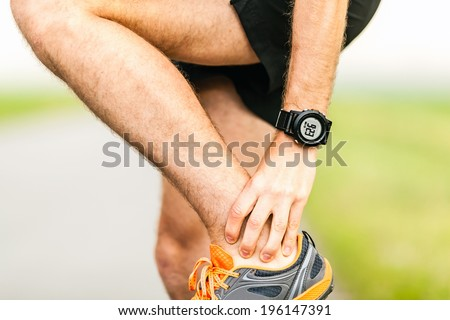 Runner holding sore leg, knee pain from running or exercising, jogging injury or cramp, cross country in summer nature - stock photo