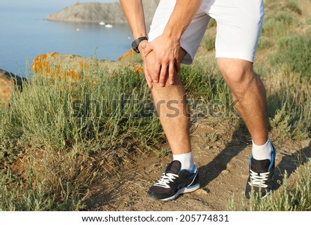 Runner holding sore leg, knee pain from running or exercising, jogging injury or cramp, cross country in summer nature. Caucasian male with tendon ache injured. - stock photo