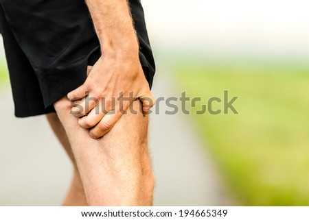 Runner holding sore leg, pain from running or exercising, jogging injury or cramp, cross country in summer nature. Caucasian male with tendon ache injured. - stock photo