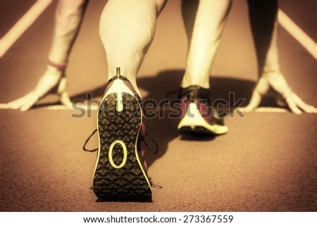 Runner in a stadium is in start position with hands on the line, interpreted as an old film. - stock photo