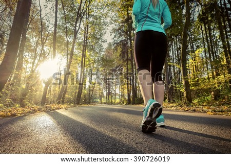 Runner in action at autumn. - stock photo