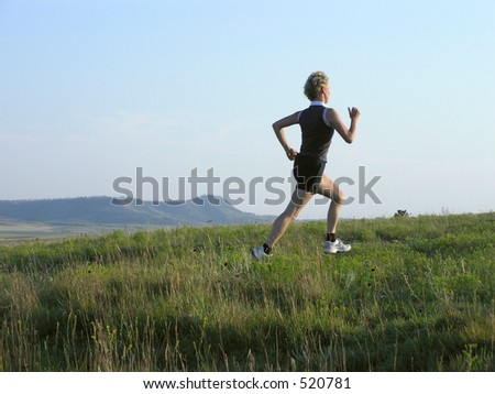 Runner in field at sunset - stock photo