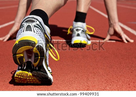 Runner in stadium waits for his start - stock photo