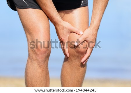 Runner injury - Man running with knee pain. Close-up view of runner injured jogging on the beach clutching his knee in pain. Male fitness athlete. - stock photo