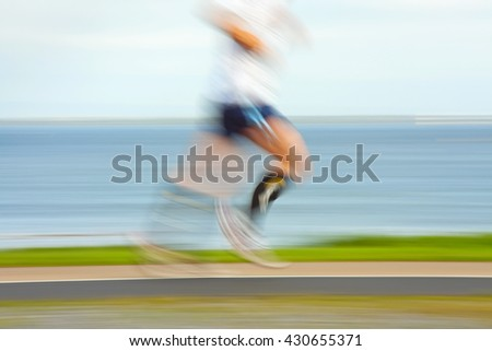 Runner jogging by the ocean coast, blurred motion. People  are not recognizable