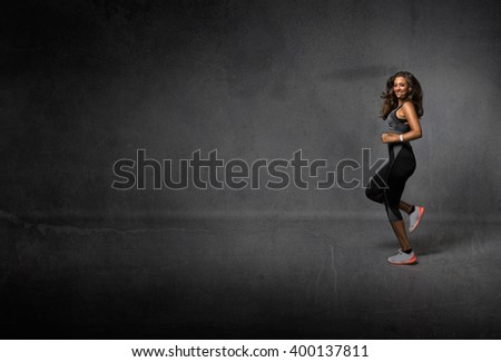 runner jogging with smile on face, dark background - stock photo