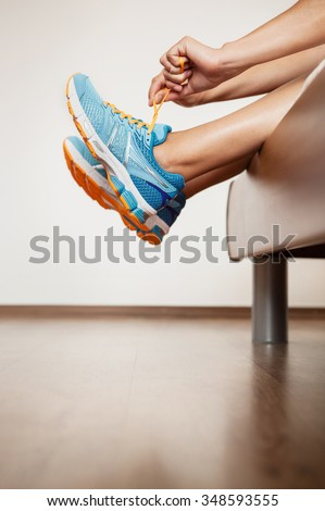 Runner lace her run shoes sitting in bed - stock photo
