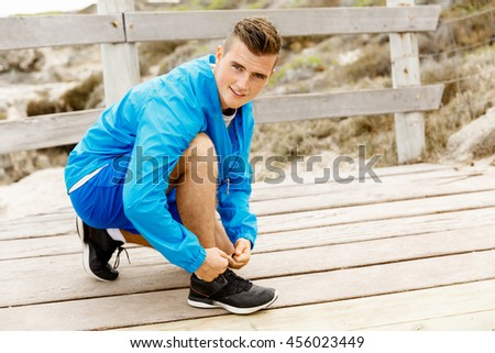 Runner laces his shoes and prepares to jogging - stock photo