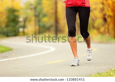 Runner legs and running shoes. Woman jogging in fall colors on forest path. - stock photo
