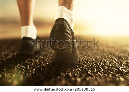 Runner legs on the road at sunrise, close up - stock photo