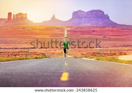 Runner man athlete running sprinting on road by Monument Valley. Concept with sprinter fast training for success. Fit sports fitness model working out in amazing landscape nature. Arizona, Utah, USA. - stock photo