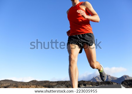 Runner man closeup - male athlete running on road sprinting. Unrecognizable person under blue sky. - stock photo