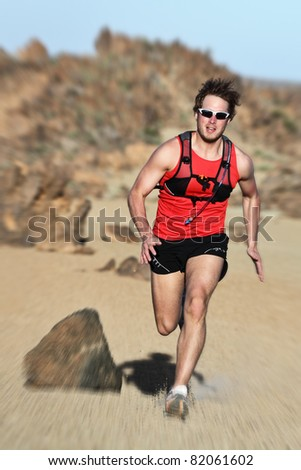 Runner. Man running fast in dramatic desert landscape. Fit fitness trail runner sprinting at high speed. Caucasian male model outside. - stock photo