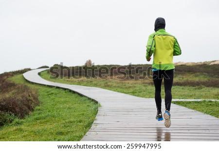 Runner man running in a rainy day. Man is running on a boardwalk - stock photo