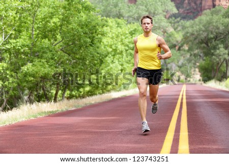 Runner man running on road training sprint for marathon run. Sporty fit caucasian male fitness sport model working out outside in full length. - stock photo