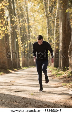 Runner man running on road training sprint for marathon run. Sporty fit caucasian male fitness sport model working out outside in full length.