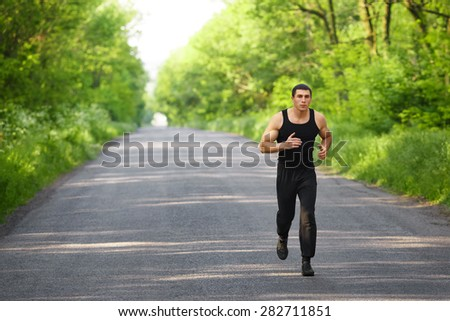 Runner man running on road training sprint. Sporting male run working out outside - stock photo