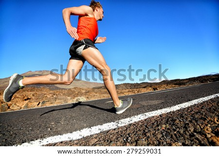 Runner man running sprinting for success on run. Male athlete runner training at fast speed. Muscular fit sport model sprinter exercising sprint on mountain road. Full body length of Caucasian model. - stock photo