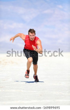Runner - man running sprinting outdoor in desert nature. Fit athlete in fast sprint run at great speed towards camera. Male fitness model training and working out in amazing extreme desert landscape. - stock photo