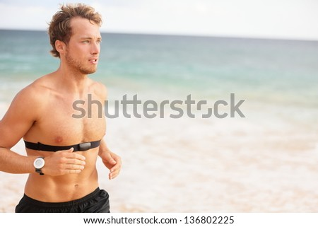 Runner man running with heart rate monitor on beach topless. Fit Fitness athlete model jogging training for marathon run outside. Young male caucasian in his twenties - stock photo