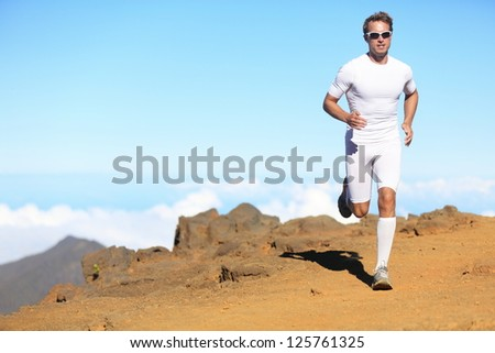 Runner man trail running in scenic landscape nature in compression clothing. Young fit male fitness athlete training outdoor for marathon. - stock photo