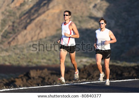 Runner men running marathon training run on road in amazing mountain landscape. Two men jogging in sporty outfit. - stock photo