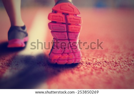 runner on a track with a close up of the shoes mid-stride on the pavement with an instagram filter (shallow depth of field) - stock photo