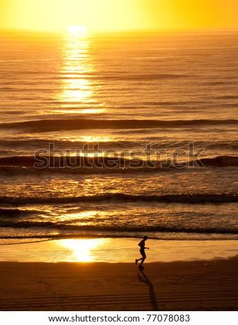 Runner on beach at sunrise - stock photo