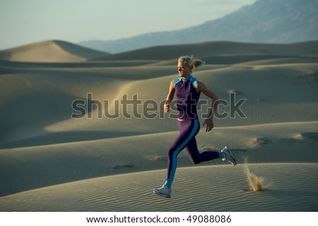 Runner on dunes in a valley - stock photo