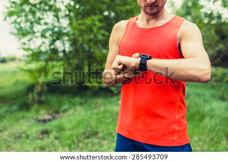 Runner on mountain forest trail checking looking at sport watch smart watch, cross country runner checking performance GPS position or heart rate pulse. Sport equipment in use outdoors on summer trail - stock photo