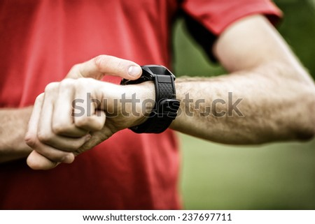 Runner on mountain trail looking at smartwatch or sport watch, checking gps navigation position map or heart rate pulse trace, using heart monitor equipment. Sport and fitness outdoors in nature. - stock photo