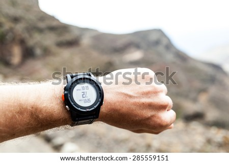 Runner on mountain trail looking at sports watch, checking GPS position, performance or heart rate pulse and training working out. Healthy lifestyle, sport and fitness outdoors in nature. - stock photo