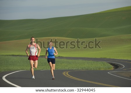Runner on rural road in farm land - stock photo