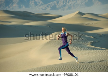 Runner on sand dunes in valley - stock photo
