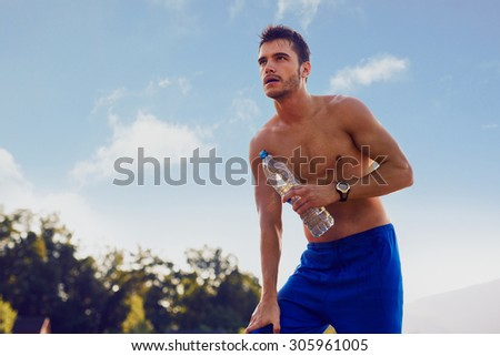 Runner resting with bottle of water in hand after intense workout - stock photo