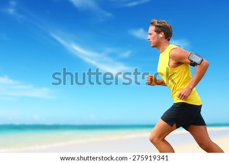 Runner running listening smartphone music on beach cardio workout. Male athlete jogging on ocean beach or waterfront working out with smart phone app device and earphones in summer. - stock photo