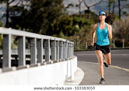 runner running over a bridge alone the road, training for fitness and marathon healthy lifestyle athlete with headphones - stock photo