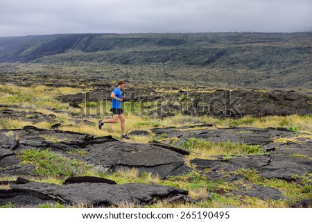 Runner. Sport running man in cross country trail run. Male athlete exercising and training outdoors in beautiful mountain nature landscape. - stock photo