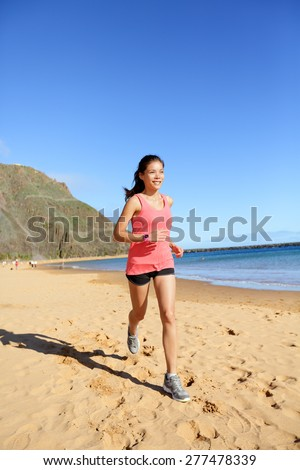 Runner sports athlete running woman on beach sweating and jogging. Fit exercising female fitness model working out training for marathon run. Biracial Asian Caucasian sports girl. - stock photo
