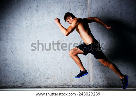Runner sprinting against concrete wall - stock photo