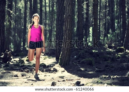 Runner stretching out during running. Beautiful young woman athlete. Caucasian / Asian female model - stock photo