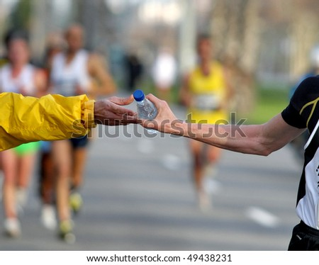 Runner take a bottle of water in a long distance race - stock photo