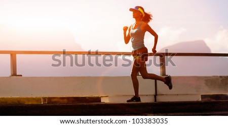 runner training at sunset, silhouette of fitness marathon woman with lens flare and action - stock photo