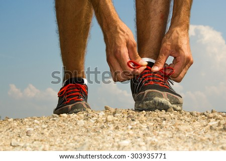 Runner tying his shoelaces before training - stock photo