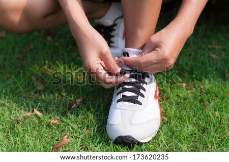 Runner tying running shoes. Woman jogging during outdoor