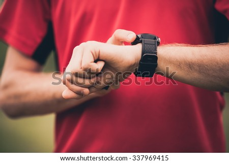 Runner using heart rate monitor training running, smartwatch checking performance or GPS. Man athlete looking at stopwatch. Healthy runner closeup on running workout. Technology for tracking activity. - stock photo